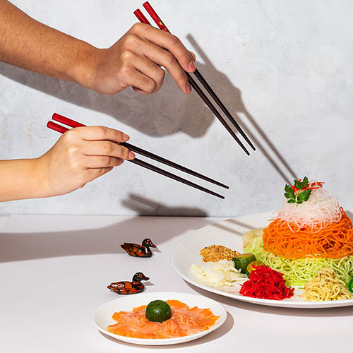Four hands with chopsticks reaching for large plate of salad with salmon dish in front