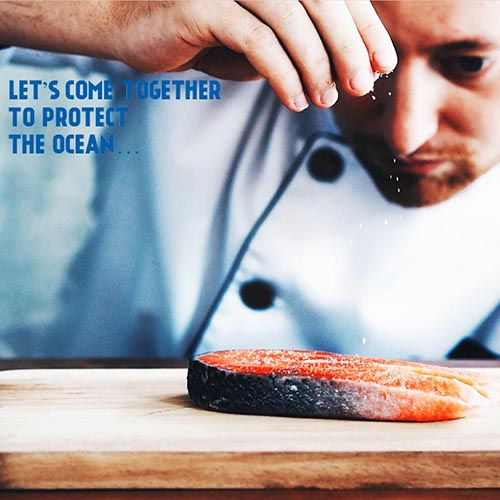 """Chef sprinkling salt on salmon with caption """"Let's come together to protect the ocean"""""""
