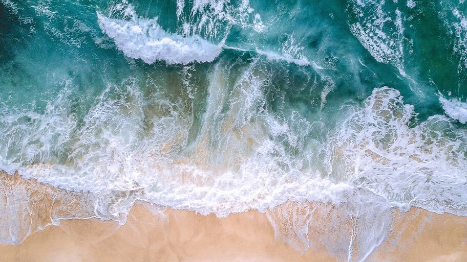 Aerial view of ocean crashing on shoreline