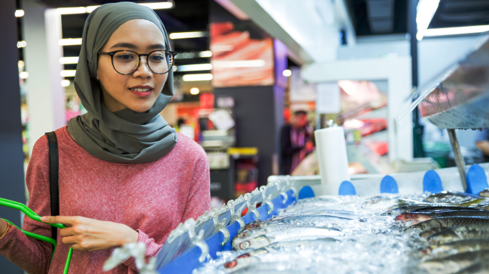 Woman wearing hijab and glasses holding shopping basket looking at fresh fish counter