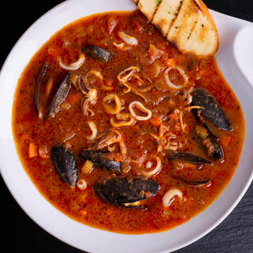 A closeup of red seafood stew in a white bowl with a small slice of bread.