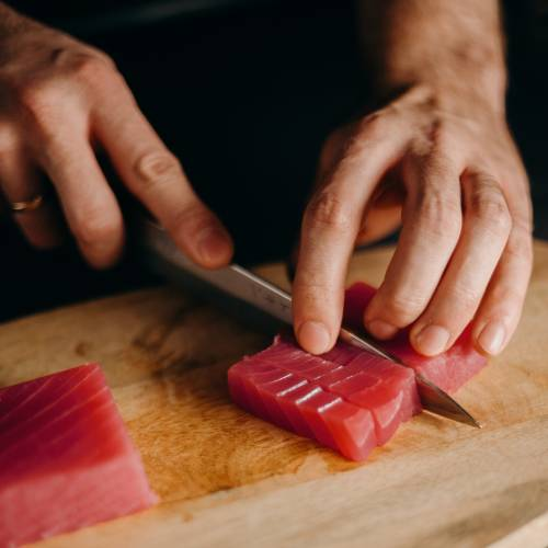 A person cutting raw tuna into thin slices on a wooden cutting board.