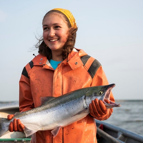 Female fisherman smiling while holding a freshly caught salmon