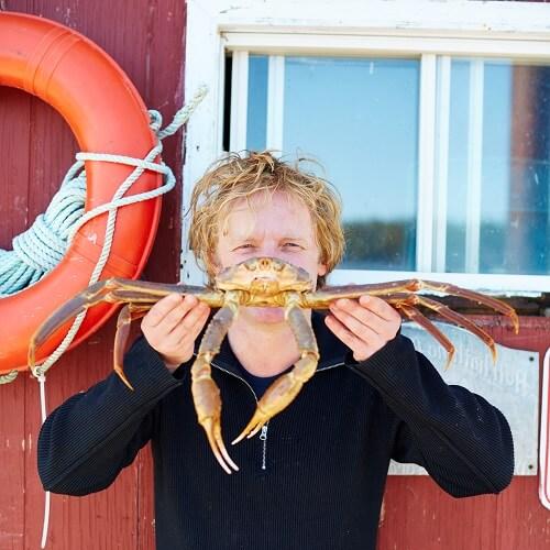 Foto van Bart van Olphen met een krab voor zijn gezicht.