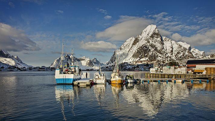 Fiskebåtar i förgrunden. Snöklädda berg och blå himmel i bakgrunden.
