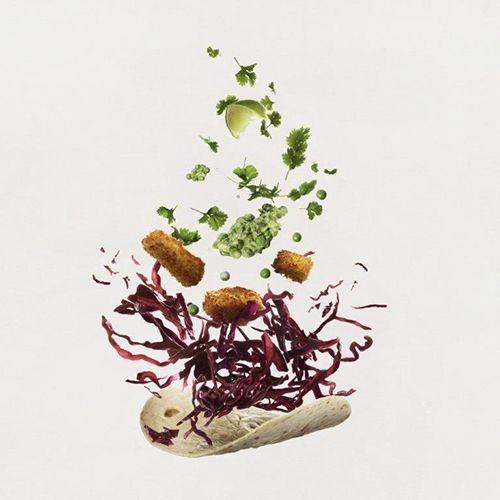 Taco med flygande fiskbitar, strimlad kål, ärtor, persilja och lime. Grå bakgrund.