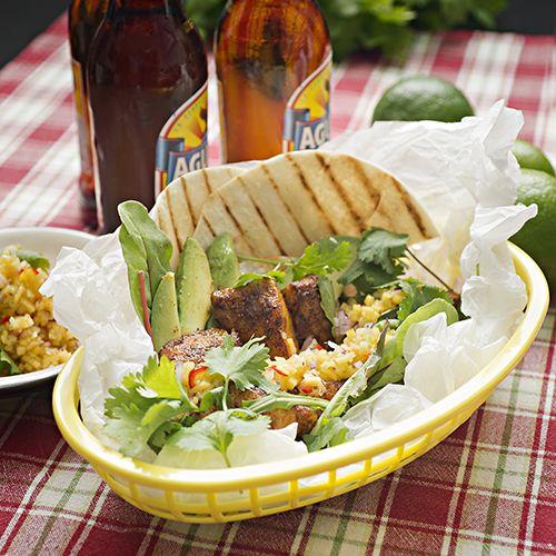 Fish tacos i en gul nätkorg. Står på en rödvitrutig duk med 2 flaskor i bakgrunden.