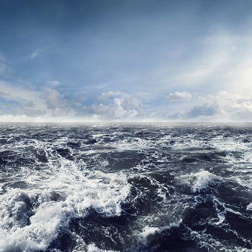 Blått hav med vågor och skum och horisont i bakgrunden.