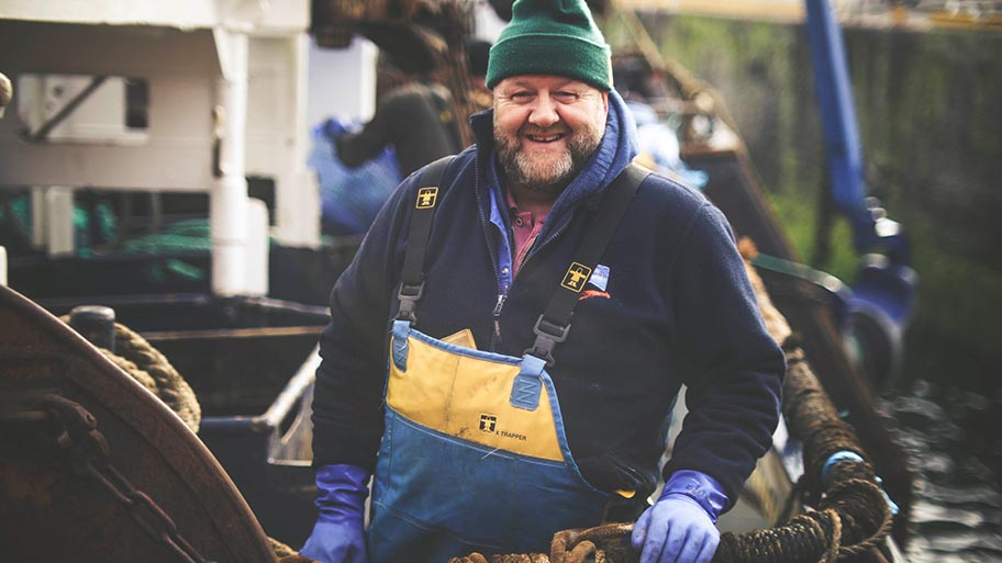 Fisherman in hat and protective clothing smiling at camera