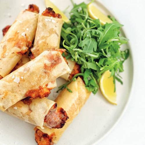 A number of fried tuna spring rolls with a rocket garnish on the side.